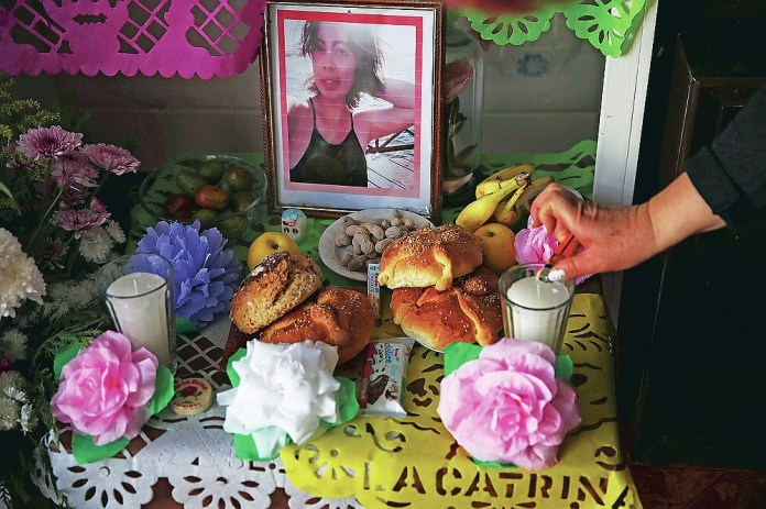 """Eulogia Herrera lights candles on a Day of the Dead altar featuring pictures of her daughter Mariana Luna Herrera who she said died of complications related to COVID-19, and who also had leukemia, at their home in Valle de Chalco on the outskirts of Mexico City, Friday, Oct. 30, 2020. Mexican families traditionally flock to local cemeteries to honor family members who died as part of the """"Day of the Dead"""" holiday, every Nov. 1 and 2, but according to authorities cemeteries will be closed this year to help slow the spread of COVID-19. (AP Photo/Marco Ugarte)"""