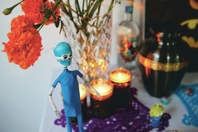 A paper skeleton dressed as a doctor adorns a Day of the Dead altar for Daniel Silva Montenegro, a doctor who died from symptoms related to COVID-19, made by his wife Kenya Navidad at her home in Mexico City, Saturday, Oct. 31, 2020. The weekend holiday isn't the same in a year so marked by death in a country where more than 90,000 people have died of COVID-19, many cremated rather than buried and with cemeteries forced to close. (AP Photo/Ginnette Riquelme)