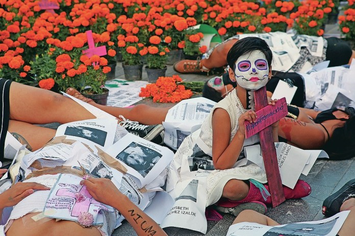 """A girl is surrounded by women dressed as """"Catrinas"""" during a performance to demand justice for victims of femicide on Day of the Dead in Mexico City, Sunday, Nov. 1, 2020. (AP Photo/Ginnette Riquelme)"""