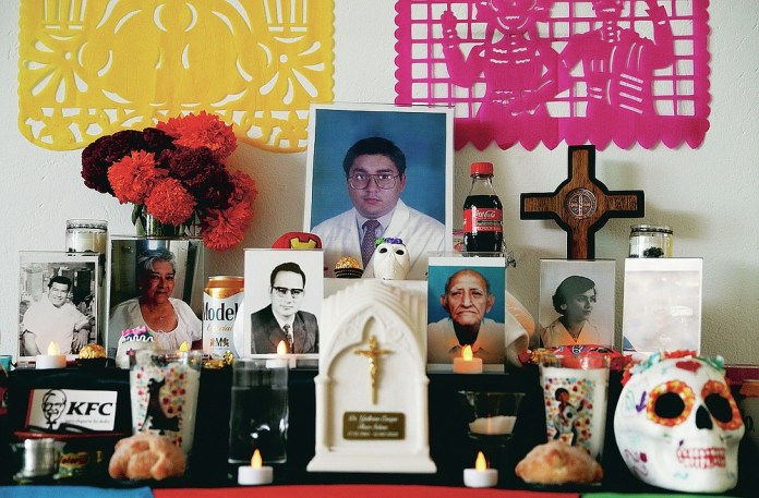 A portrait of Dr. Guillermo Flores, who died from symptoms related to COVID-19, is placed on a Day of the Dead altar made by his wife, Alexandra Valverde, at their home in Mexico City, Sunday, Nov. 1, 2020. He is one of more than 1,700 Mexican health workers officially known to have died of COVID-19 who are being honored with three days of national mourning on these Days of the Dead. (AP Photo/Eduardo Verdugo)