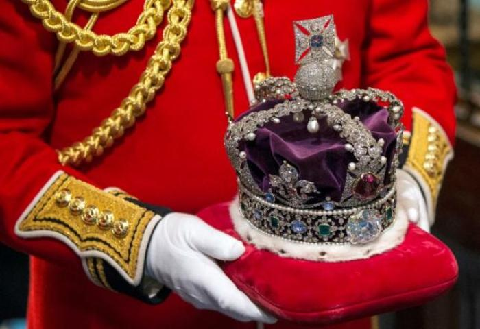 Britain's Queen Elizabeth's crown is carried through the Norman Porch of the Palace of Westminster after the State Opening of Parliament on June 4, 2014 in London, England. REUTERS/POOL/Oli Scarff