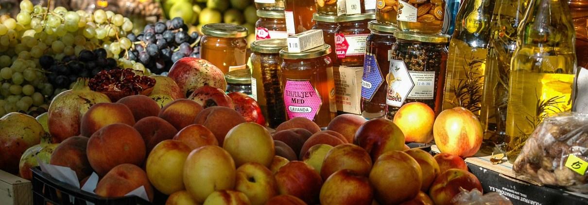 Marktstand mit Aepfeln, Honig, Oelen