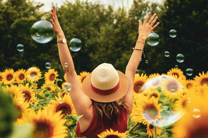 woman with raised arms among sunflowers and bubbles