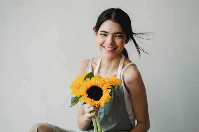 woman holding sun flowers smiling