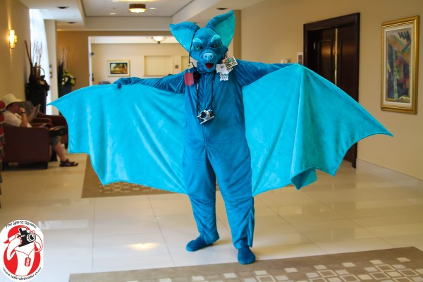 A flying furry makes its way down the convention hall corridor taking a moment for a photo opportunity © 2014 by John N. Collins
