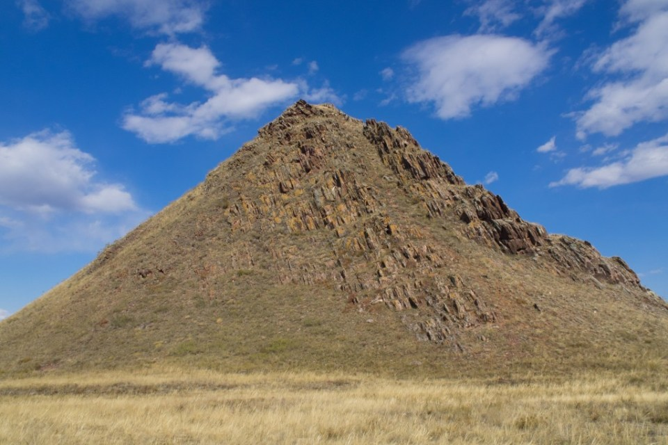 """Syyn-Churek mountain is situated on the 150th kilometer of the route Kyzyl - Ak-Dovurak. Syyn-Churek means """"a heart of a deer"""". The mountain reminds a pyramid.   There are more than 300 paintings on the southern and south-eastern slopes of the mountain. These paintings take a special place among all the ancient monuments of Tuva. The paintings depict tigers, horses, antelopes, goats, people and solar signs. Photo by  Rita Willaert"""