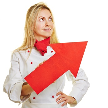 Lächelnde Köchin in Arbeitskleidung mit einem roten Pfeil nach oben