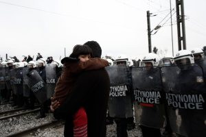 epa05232701 A Syrian refugee child looks as her father carry her in front of riot police during a protest organised by refugees and migrants demanding the opening of the borders at the refugee camp of Idomeni near the Greek-Former Yugoslav Republic of Macedonia (FYROM) borders in northern Greece, 27 March 2016. Migration restrictions along the so-called Balkan route, the main path for migrants and refugees from the Middle East into the European Union, has left thousands of migrants trapped in Greece. EPA/KOSTAS TSIRONIS