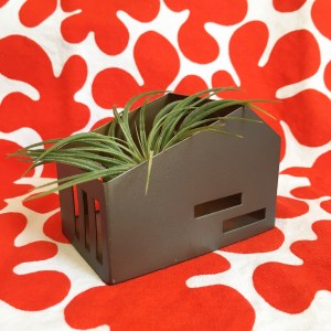 welcome objects avatar, an airplant inside a house-shaped candle holder, against a Marimekko print.