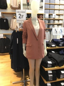 Uniqlo 2017 drape collection long jacket in a dusty pink color, as displayed on a mannequin in a store.