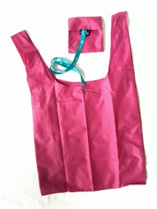 Pink standard Baggu with a cord attaching the bag to its pouch.