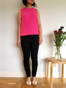 Victoria Beckham for Target fuchsia sleeveless top as modeled on me with black jeans. Next to me is a vase with flowers.