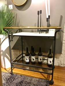CB2 Cavalier bar cart. It has black and gold metal and glass shelving.