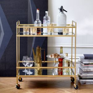 West Elm terrace bar cart, art deco style. It has mirrored shelves and gold metal.