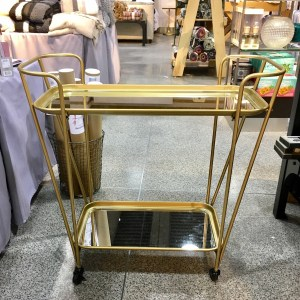 Gold metal mirrored bar cart in the store. The bottom shelf is mirrored.