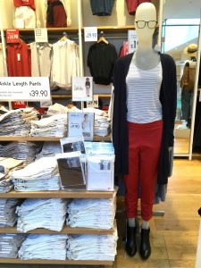 Mannequin at a Uniqlo store wearing a black and white striped shirt and smart ankle length pants in red.