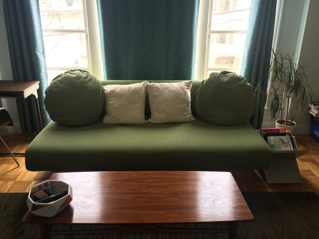 IKEa Allerum sofa bed, light green in color, with two round pillows.