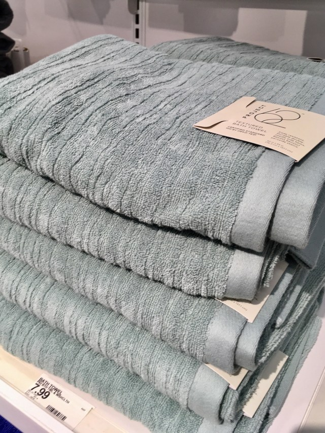 Stack of textured bath towels in a blue green color, on display on a shelf.
