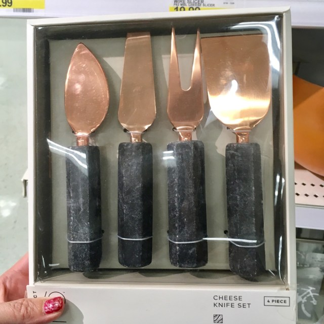 Cheese knife set in a box. The blades are rose gold. The handles are marble-like.