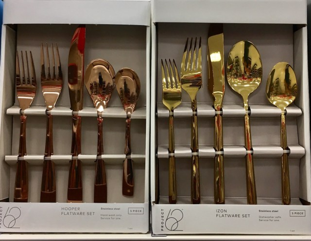 2 boxes of flatware, one in rose gold and one in gold.