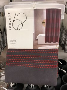 Gray shower curtain with red embroidered dash lines, as shown folded up and hanging on a hanger in a store.