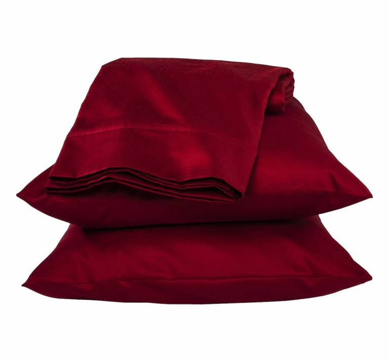 A stack of two pillows in pillow cases plus sheets folded up on top of them. They are red.