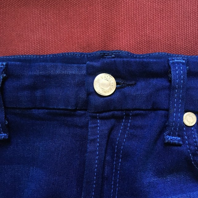 Close up of fly and button of a pair of blue jeans.