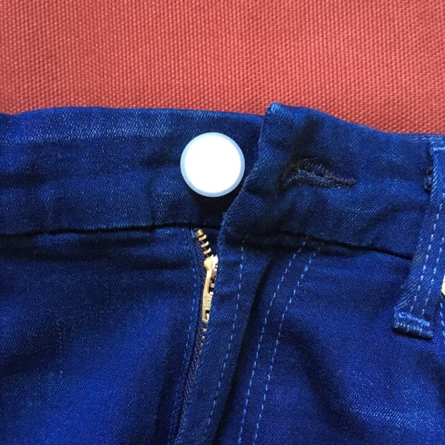 Closeup of blue jeans with Holé button cover.