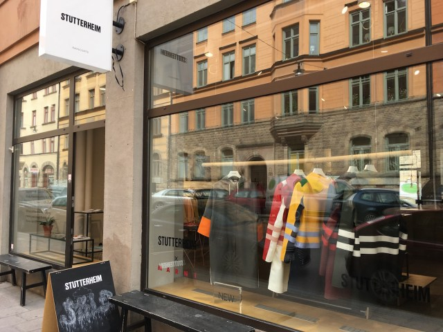 Exterior of the Stutterheim store. Display by the window shojes some jackets on a rack. There is a bench right outside the window.