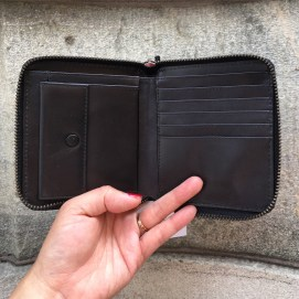 A hand holding open a zippered square wallet. The wallet has a coin pocket, five credit card slots, 2 additional slots, and a paper cash slot.