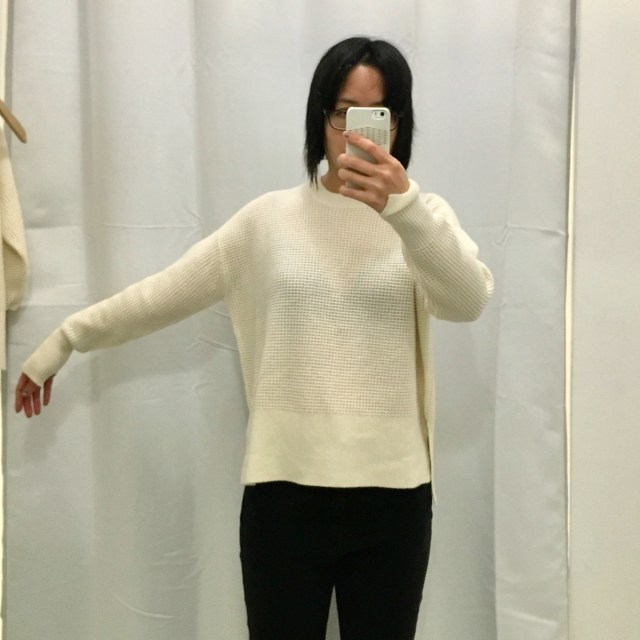 Everlane waffle knit square sweater as worn on me, a petite Asian woman. One arm is held out to show how roomy the sweater is.