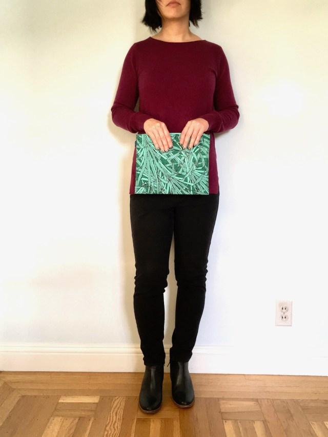 A woman holds a large nylon pouch in front of her. It is large enough to serve as a clutch purse. The pouch has a frond print.