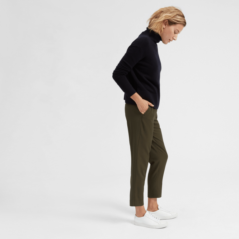 A model wears the Everlane GoWeave Easy Pant in olive green with white sneakers and a black sweater.