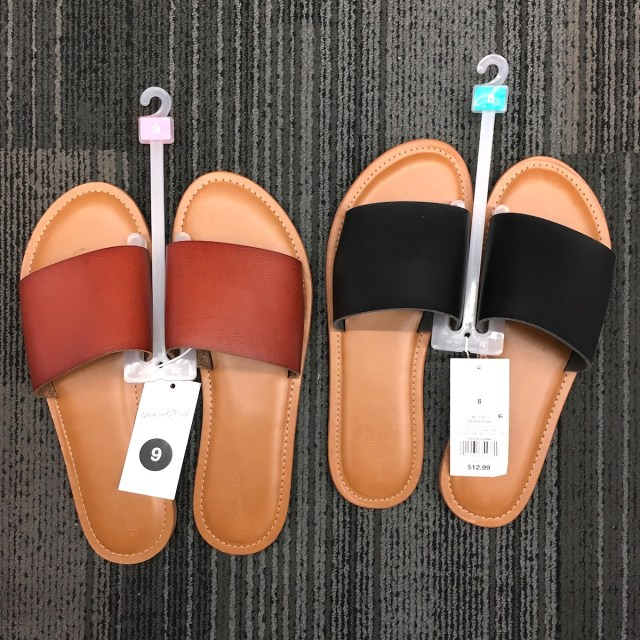 Two pairs of slide sandals on the carpeted floor at Target. One is cognac color and the other is black.