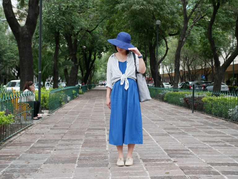 How to pack light for vacation: A woman stands on a brick walkway. She's wearing a mid dress, a long sleeve shirt tied at the front, and a hat.