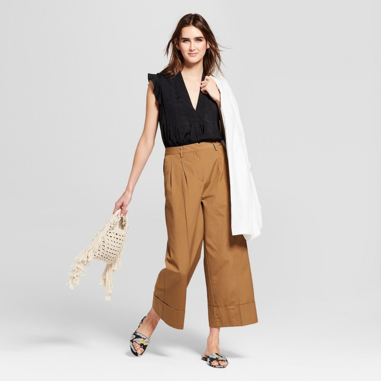 A stock photo from Target showing a model, a white woman, wearing brown wide leg pants with a black top.