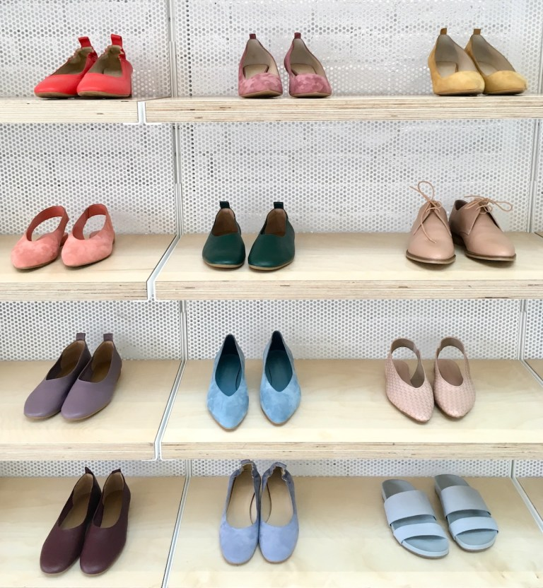Shelves with shoes on display at Everlane. They are of various colors: orange, pink, green, blue.
