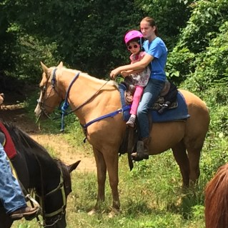 """Nat's first horse ride. Riding tandem with instructor on """"Nugget""""."""