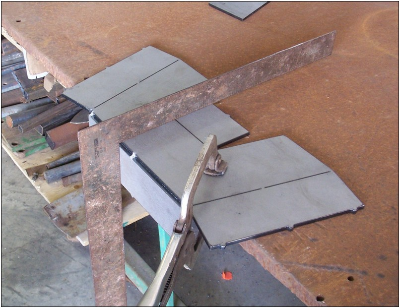 Clamp the plate to your bench, then use an adjustable wrench to fold the top to 90 degrees.