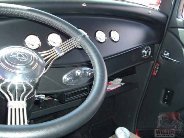 An under-dash shelf in a roadster is a good way to make use of the space. A 'secondary' dash drops down from the main dash with the same curve.