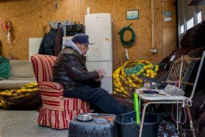 old fisherman repairing nets in Portugal