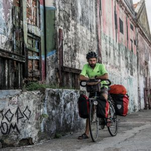 Cyclist next to graffiti walls of a warehouse