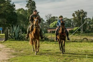 Traditional gaucho with his son riding on a horse