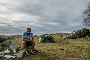 Cyclist cooking diner on a camping stove next to the tent