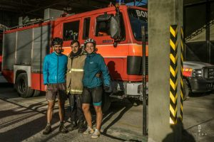 Three man posing in front of a fireman truck