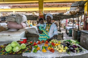 Mother with a child selling vegetables on the market in Gambia