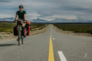 Belgian cyclist on ruta 40 with beautiful snow capped mountains