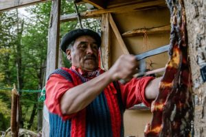 Traditional Chilean gaucho sawing dried meat