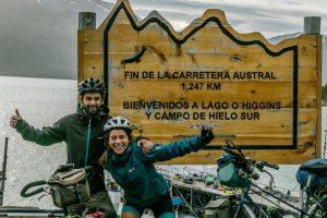 Cyclists posing in front of Fin de La Carretera Austral sign in Villa O'Higgens