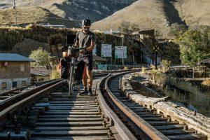 Cyclist Walking on the train tracks